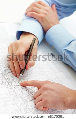 Close-up of engineers hands with pens over blueprints with sketches of projects - stock photo