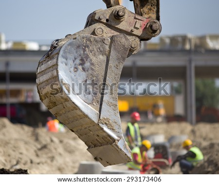 Close up of excavator bucket in the air at construction site and workers  in background - stock photo