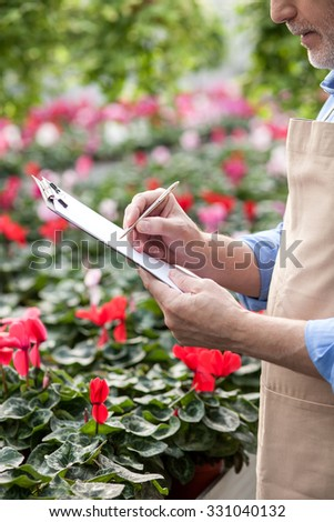 Close up of experienced senior gardener is writing notes into folder of documents seriously. He is standing at greenhouse  - stock photo