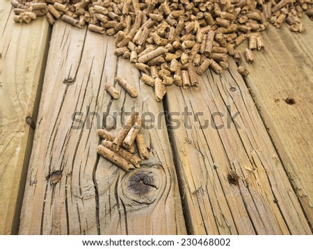 close up of extruded wood pellets on old cracked knotted wooden board with wood pellets out of focus behind - stock photo
