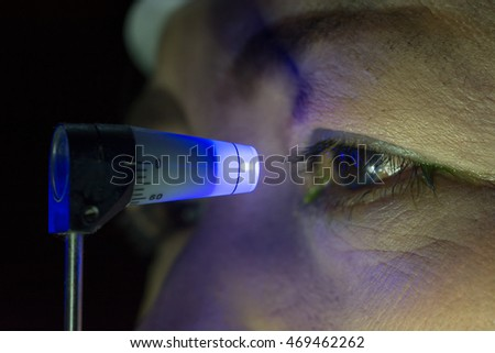 Close up of eye examination, ocular pressure measurement with applanation tonometer in dark room.