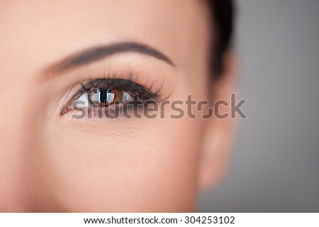Close up of eye of pretty woman looking forward with passion. She has perfect skin. Isolated and copy space in right side - stock photo