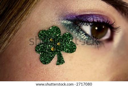 close-up of eye with shamrock underneath, focus on the shamrock - stock photo