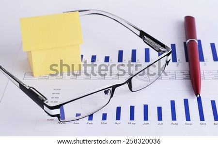 Close up of eyeglass and pen with house paper on chart for Loans money concept