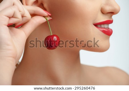 Close up of face of attractive girl raising cherry to her ear. She is smiling in profile - stock photo