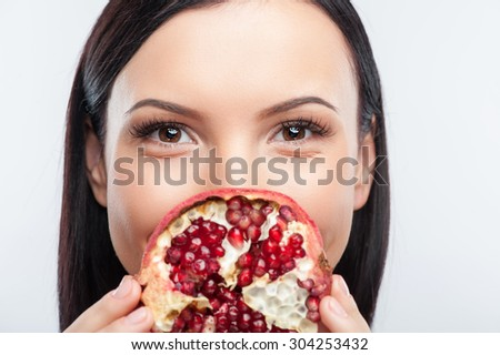 Close up of face of cheerful girl is covering her mouth with a part of pomegranate. She is looking at the camera with joy and smiling. Isolated on background - stock photo