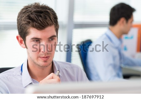 Close-up of face of manager sitting at computer - stock photo