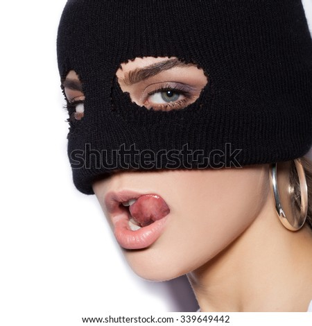 Close-up of face of sexy woman in balaclava - crime and violence on white background not isolated - stock photo
