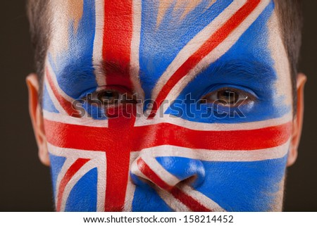 Close-up of face with face art on it. Flag of Great Britain on black background