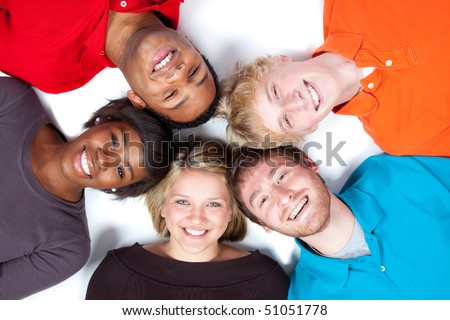 Close-up of faces of Multi-racial college students/friends lying on the ground - stock photo