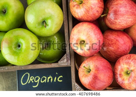 Close up of farmers crates with assorted ripe apples on a wooden background. - stock photo