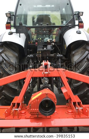 Close-up of farming tractor with equipment in red color. - stock photo
