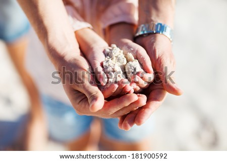 Close up of father and daughter hands holding sand  - stock photo