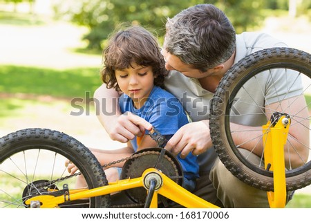 Close-up of father and son fixing bike - stock photo