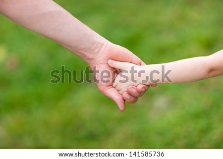 Close up of father holding his daughter hand - stock photo
