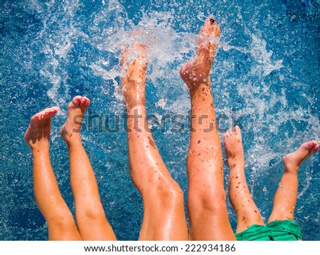 Close-up of feet of family in the swimming pool - stock photo