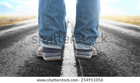 Close up of feet of man on long straight asphalt road - stock photo