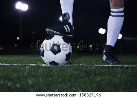 Close up of feet on top of soccer ball on the line - stock photo