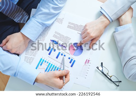 Close-up of female and male hands pointing at business document with diagrams and charts