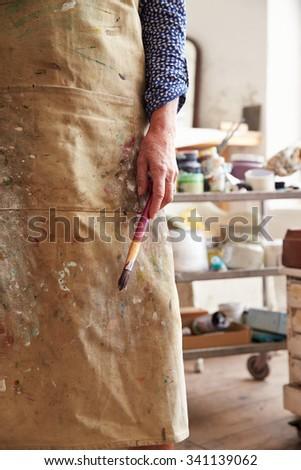 Close Up Of Female Artist Holding Brush In Studio - stock photo