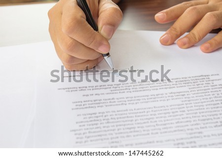 close up of female business hand signing document.