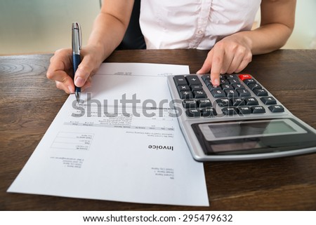 Close-up Of Female Businesswoman Calculating Tax With Calculator At Desk - stock photo