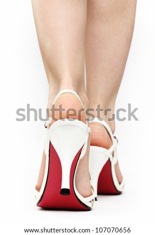Close up of female caucasian feet in white lace sandals with red sole walking isolated on white background - stock photo