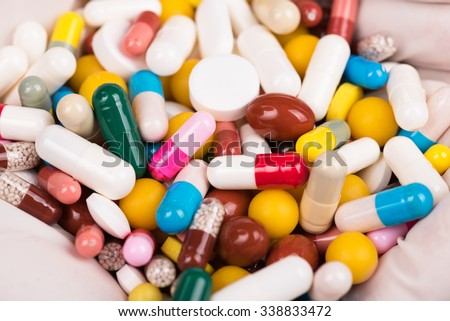 Close-up of female doctor's hand holding pills for his patient - stock photo