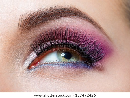 Close up of female eye with brilliant pink makeup. Concept of beauty and fashion