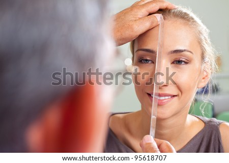 Close-up of female face being measured by plastic surgery doctor - stock photo