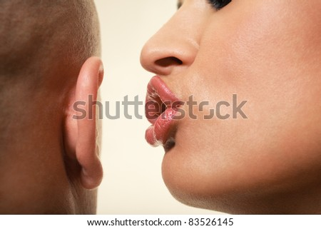 Close up of female face whispering to male ear - stock photo