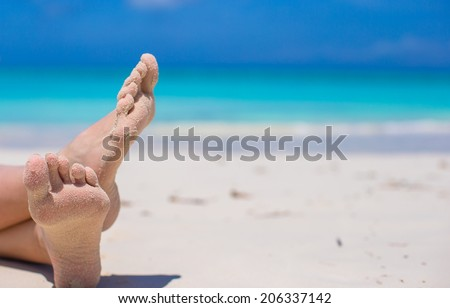 Close up of female feet on white sandy beach - stock photo