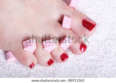 Close-up of female feet with red polished nails carefree - stock photo
