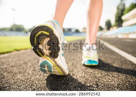 Close-up of female foots in sneakers. Sporty woman running outdoors at sunrise.