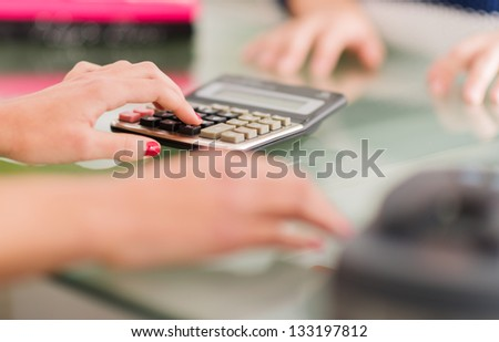 Close-up Of Female Hand Calculating, Indoors - stock photo