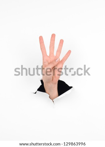 close-up of female hand coming out from a hole in a paper, counting number four gesture, isolated on white - stock photo