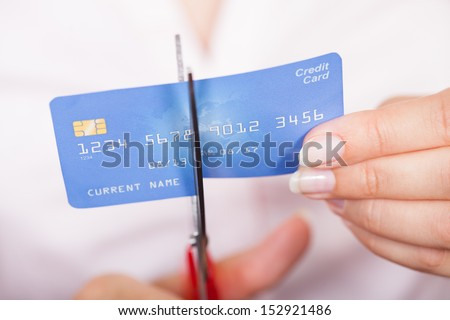 Close-up Of Female Hand Cutting Credit Card With Scissor