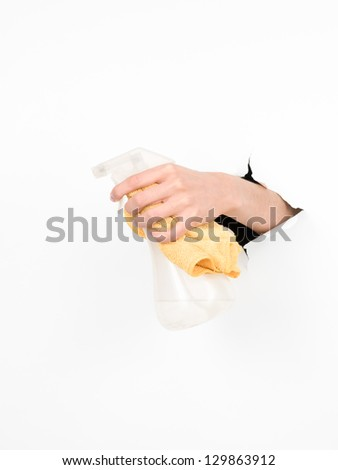 close-up of female hand holding a  liquid detergent container and a rag through a torn white paper, isolated