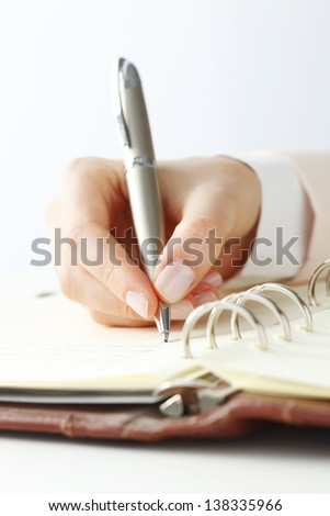 Close-up of female hand holding a pen and writing some research notes in the appointment book