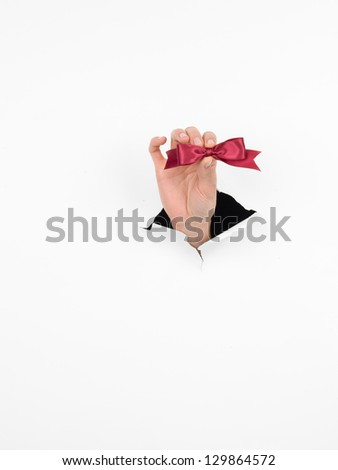 close-up of female hand holding a small burgundy shiny bow through a torn white paper, isolated - stock photo