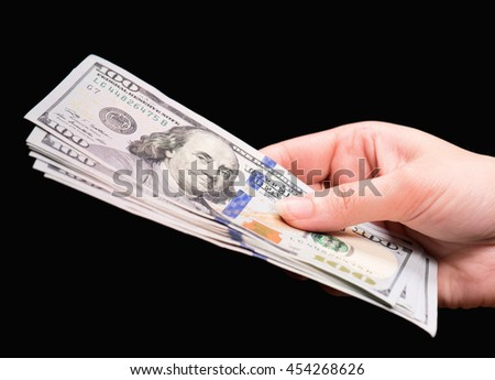 Close up of female hand holding money - US dollar banknotes against dark background - stock photo
