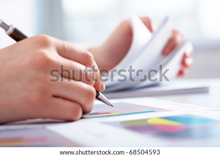 Close-up of female hand holding pen over business graph - stock photo