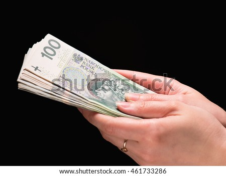 Close up of female hand holding Polish money banknotes against dark background