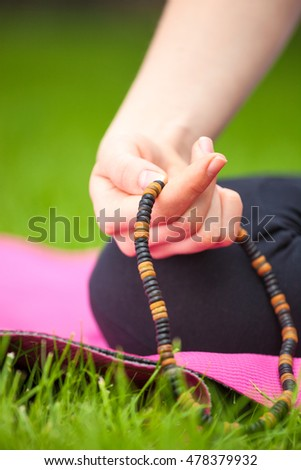 Close up of female hand holding rosary - meditation concept.