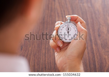 Close-up Of Female Hand Holding Stopwatch In Hand - stock photo