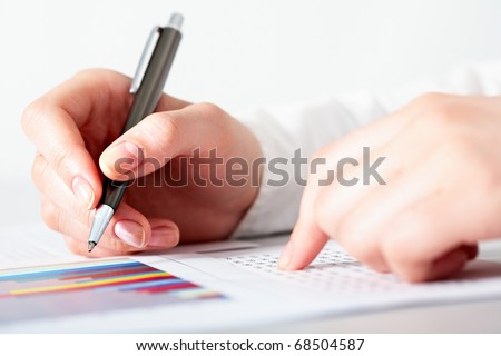 Close-up of female hand prepare for write number on graph - stock photo