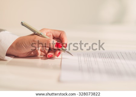 Close-up of female hand ready to sign a document - stock photo