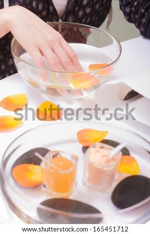 Close up of female hand soaking in glass bowl of water. Manicure and skincare. Woman in spa beauty salon. - stock photo