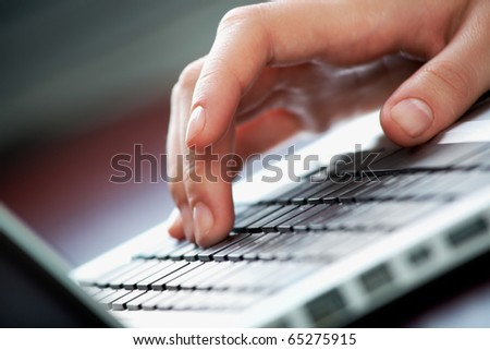 Close-up of female hand touching buttons of keyboard - stock photo