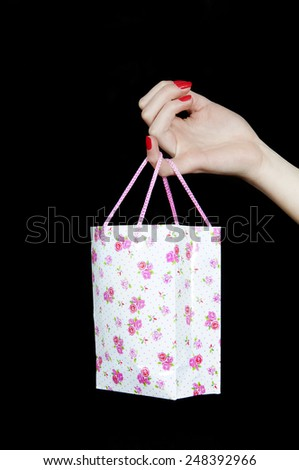 Close-up of female hand with a shopping bag on her little finger  - stock photo